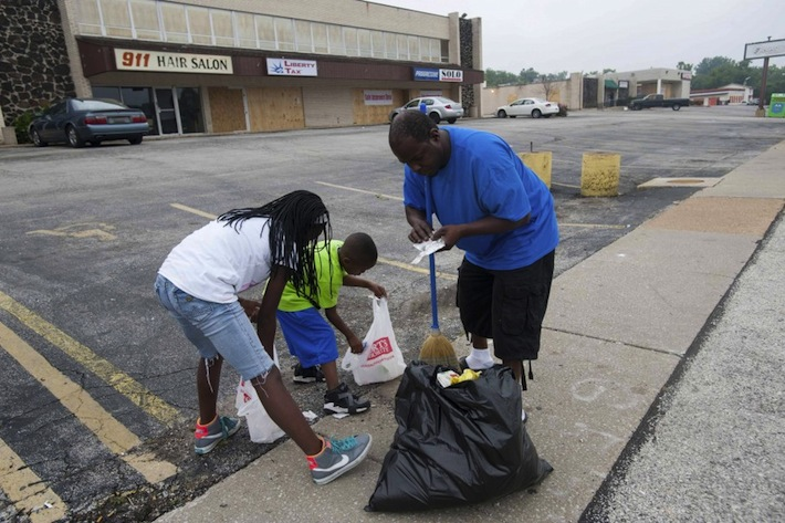 Tyrell Mosley, his daughter McKayla and his son Demarre help clean up in Ferguson. (Image: Mark Kauzlarich/Reuters)