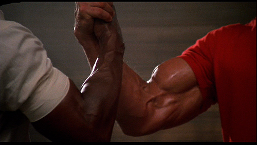 Arnold Schwarzenegger and Carl Weathers rippling biceps battle.