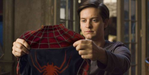 Peter Parker holding his Spider-Man suit