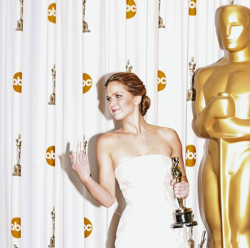 """Jennifer Lawrence reacts as she poses with her Oscar after winning the Best Actress award for her role in """"Silver Linings Playbook"""" at the 85th Academy Awards in Hollywood"""
