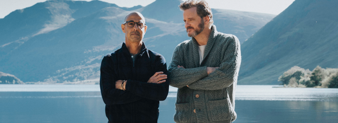 Stanley Tucci and Colin Firth stand side-by-side in from of a lake in a still from Supernova