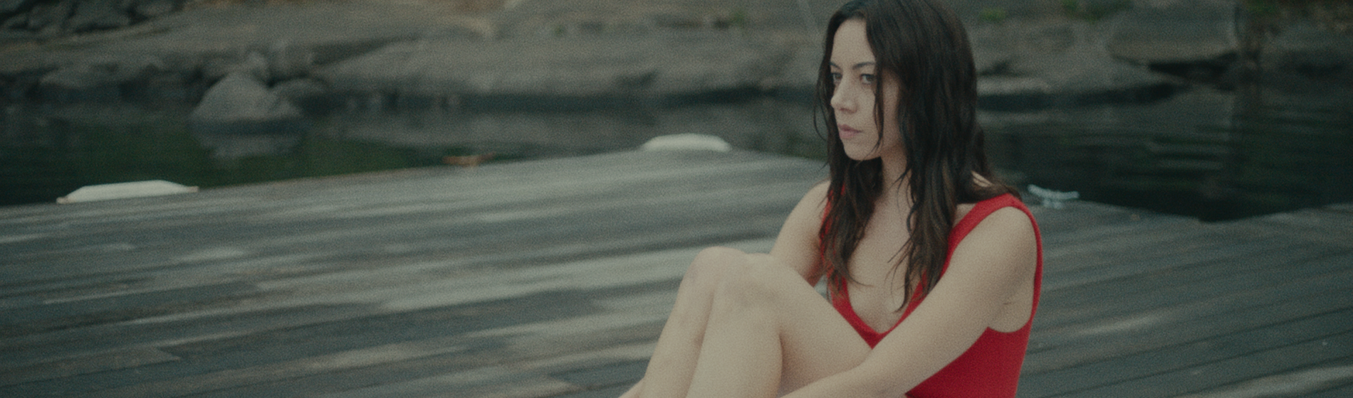 Aubrey Plaza wearing a red bathing suit sitting on a dock in a still from Black Bear