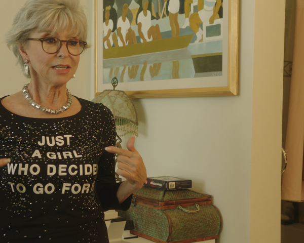 Rita Moreno pointing to her shirt, which say Just A Girl Who Decided to Go For It