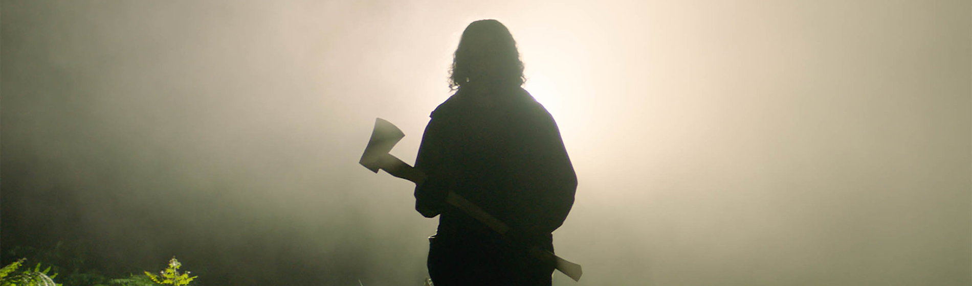 A still from In The Earth showing the silhouette of a person holding an axe.