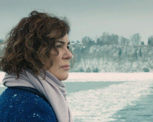 Woman in snowy landscape drifitng snow